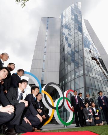 「ジャパン・スポーツ・オリンピック・スクエア」でお披露目された五輪マークの前で記念撮影する関係者=16日午前、東京都新宿区