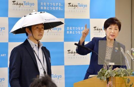 かぶるタイプの傘について説明する東京都の小池百合子知事(右)=24日午後、東京都庁