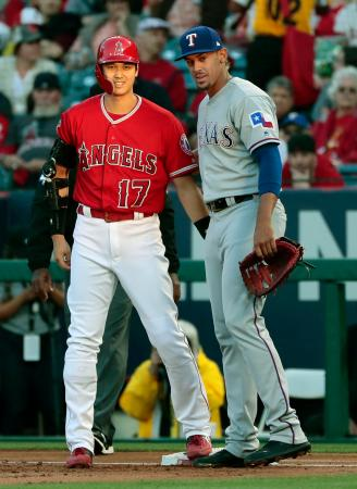 レンジャーズ戦の1回、四球で出塁し、笑顔を見せるエンゼルス・大谷(左)=アナハイム(共同)