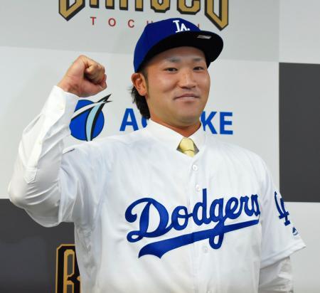 ドジャースとマイナー契約を結び、ユニホーム姿でガッツポーズする北方悠誠投手=30日、栃木県小山市