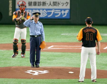 巨人―ロッテ戦で始球式を務め、敬礼する三浦正充警視総監。奥は巨人の小林誠司捕手=8日、東京ドーム