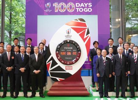 ラグビーW杯日本大会開幕まで100日の記念イベントで披露されたカウントダウン時計と写真に納まる関係者=12日午前、東京都中央区