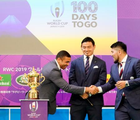 ラグビーW杯の優勝杯「ウェブ・エリス・カップ」の前で笑顔を見せる(左から)元南アフリカ代表のブライアン・ハバナさん、五郎丸歩選手ら=12日午後、東京・丸の内