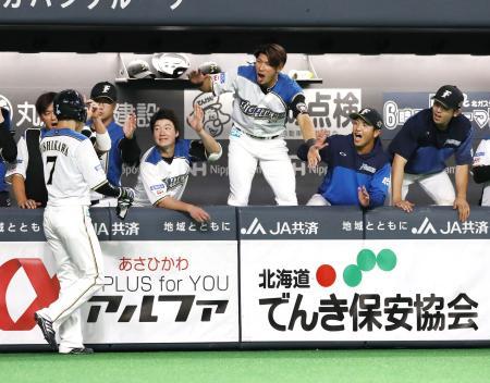 10回、王柏融の二塁打で同点の生還をした三走西川(7)を迎える日本ハムナイン=札幌ドーム