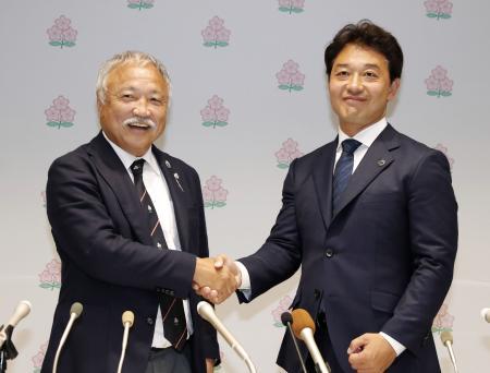 就任記者会見を終え握手を交わす、日本ラグビー協会の森重隆会長(左)と岩渕健輔専務理事=29日午後、東京都新宿区