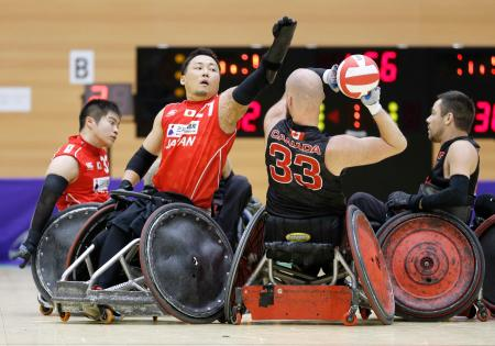 車いすラグビーのカナダ代表との試合で競り合う日本代表の池(手前左)=7日午後、青森県三沢市