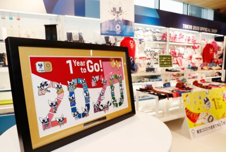 発売が開始された、東京五輪開幕1年前を記念した公式グッズ。手前左は限定生産のピンバッジ額装=11日午前、東京都墨田区の「とうきょうスカイツリー店」