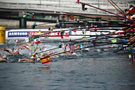 世界水泳第3日、オープンウオーター女子10キロで給水する選手たち=14日、麗水(ロイター=共同)