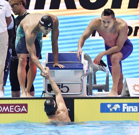 男子400メートルリレー予選 最終泳者の難波(下)を迎える中村(左)と塩浦=光州(共同)