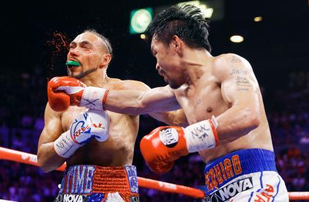 WBAウエルター級王座統一戦でキース・サーマン(左)を攻めるマニー・パッキャオ=ラスベガス(AP=共同)