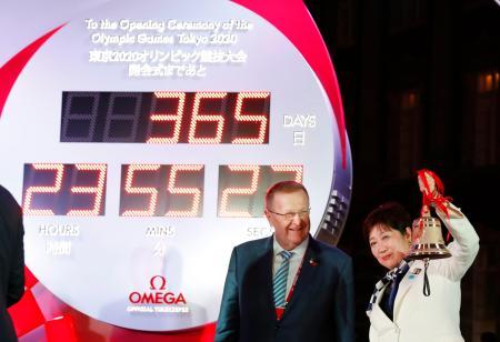 東京五輪の開幕まで1年となり、JR東京駅前に設置された「カウントダウンクロック」の前でベルを鳴らす東京都の小池百合子知事。左はIOCのコーツ調整委員長=24日夜、東京・丸の内