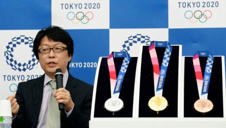 記者会見で東京五輪のメダルデザインに込めた思いを話すデザイナーの川西純市さん=25日午前、東京都中央区