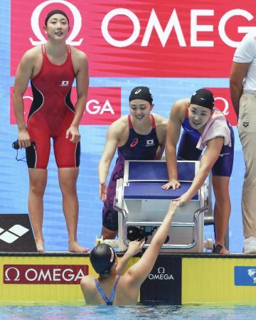 女子800メートルリレー予選を終え、最終泳者の池本(下)とタッチする(上左から)五十嵐、青木智、白井。東京五輪出場枠を獲得した=光州(共同)
