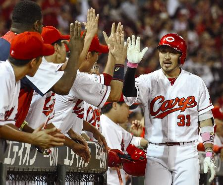 5回、本塁打を放ち、ナインに迎えられる広島・菊池涼=マツダ