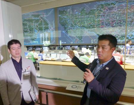 警視庁の交通管制センターで首都高速道路の混雑状況を説明する東京五輪大会組織委の輸送担当者(右)=26日午前