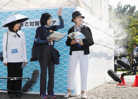 ビーチバレーの五輪テスト大会の会場を訪れ、大型ミストタワー(後方)など暑さ対策を視察する東京都の小池百合子知事(右)=28日午後、東京都品川区