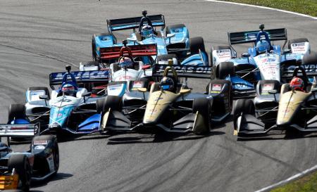 インディカー・シリーズ第13戦、コーナーで競り合うホンダの佐藤琢磨(左)=28日、レキシントン(AP=共同)