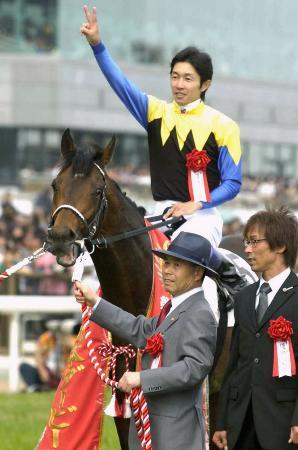 デビューから無敗で日本ダービーを制したディープインパクトと記念撮影に納まる武豊騎手。前列左は、調教師の池江泰郎さん=2005年5月、東京競馬場
