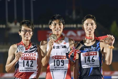 日本選手権の男子5000メートルで優勝し、表彰台でメダルを掲げる松枝博輝(中央)。左は2位の田中秀幸、右は3位の服部弾馬=博多の森陸上競技場