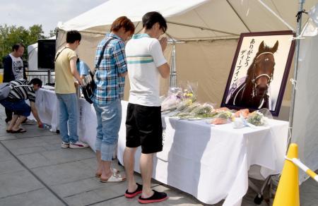 札幌競馬場に設置されたディープインパクトの献花台で手を合わせるファンら=3日午前