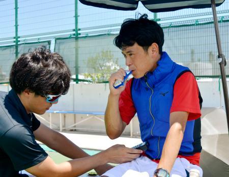 暑さ対策のテストで、試合の休憩時に冷却剤を入れたベストを着用し、アイススラリーを口にする大学生=5日、三重県四日市市