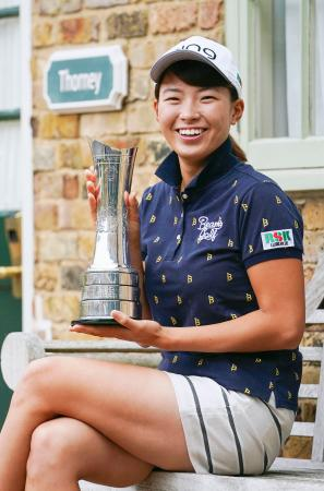 ゴルフのAIG全英女子オープン優勝から一夜明け、トロフィーを手に笑顔の渋野日向子=5日、英ミルトンキーンズ(共同)