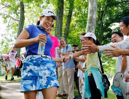 女子ゴルフの北海道meijiカップ最終ラウンド、9番に向かう途中に子どもたちと笑顔でタッチする渋野日向子=11日、北海道北広島市の札幌国際CC