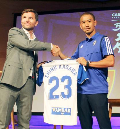 スペイン2部リーグのサラゴサに移籍加入し、チーム関係者(左)と握手する香川真司=13日、サラゴサ(共同)