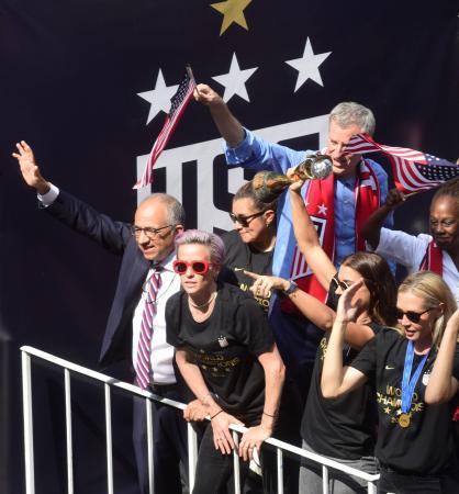 サッカー女子W杯優勝パレードで歓声に応える(左手前から)米国サッカー連盟のコルデイロ会長、ラピノーら米国選手=7月、ニューヨーク(ロイター=共同)
