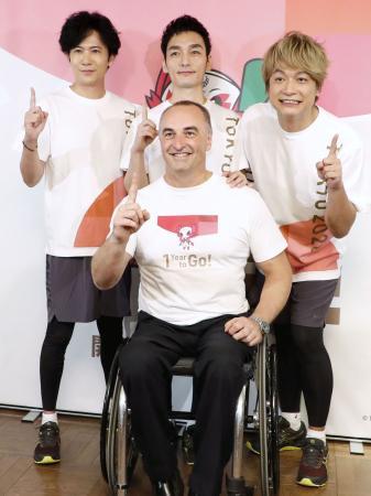 笑顔で写真撮影に応じる、IPCのドゥエーン・ケール副会長(手前)と特別親善大使の(後列左から)稲垣吾郎さん、草なぎ剛さん、香取慎吾さん=25日午後、東京都渋谷区