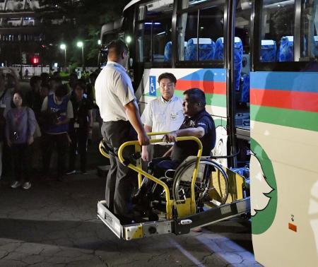 バスから降りる車いすの男性=25日午後、東京都新宿区