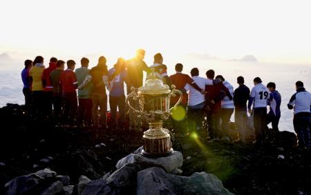 富士山の山頂に運ばれ、朝日に輝くラグビーW杯の優勝杯「ウェブ・エリス・カップ」。奥は山梨学院大のラグビー部員ら=27日午前5時19分