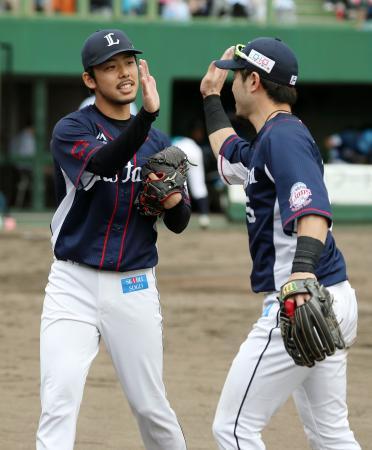 5回、ピンチをしのぎ二塁手外崎(右)とタッチを交わす西武・本田=帯広