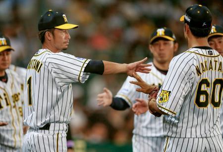 2回を終え、守備から戻った選手を迎える阪神・鳥谷(左)=甲子園