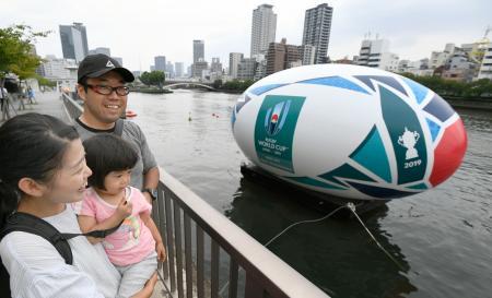 ラグビーW杯日本大会を盛り上げようと、大阪市の大川に浮かべられた全長約10メートルの巨大ラグビーボールのバルーン。多くの家族連れなどが足を止めた=1日午後