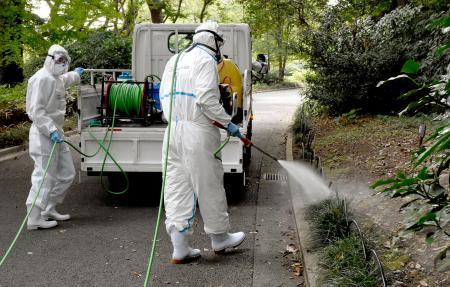 東京都の新宿御苑で行われた蚊を駆除するための殺虫剤を散布する訓練=2日午前