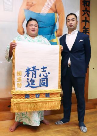 高校時代の恩師、奥谷猛さん(右)から贈られた化粧まわしを手にする朝玉勢=5日、東京都墨田区の高砂部屋