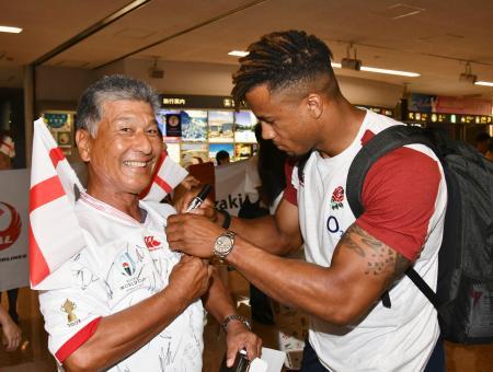 宮崎空港に到着し、ファン(左)にサインするイングランド代表の選手=10日午後