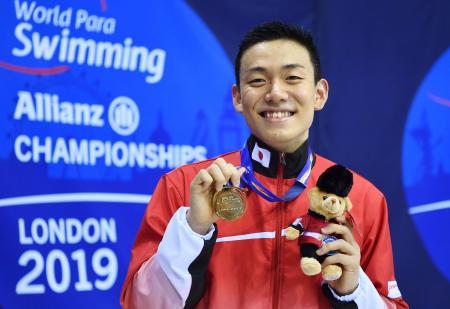 男子100メートル平泳ぎ(知的障害)の金メダルを手に笑顔の山口尚秀。東京パラリンピックの代表に決まった=ロンドン(共同)