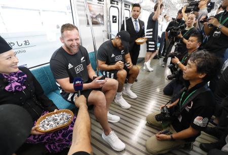 つくばエクスプレスの貸し切り電車内で笑顔を見せる、ラグビー・ニュージーランド代表のキーラン・リード主将(左から2人目)=12日午後