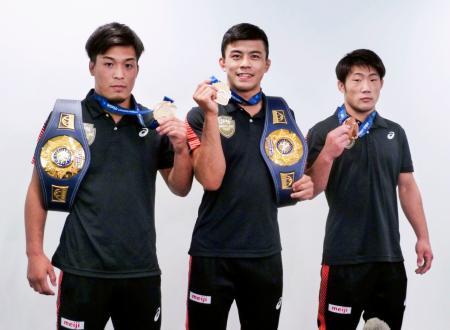 帰国し、メダルを手に撮影に応じる男子グレコローマンの(左から)63キロ級の太田忍、60キロ級の文田健一郎、55キロ級の小川翔太=20日、羽田空港