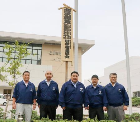 大相撲九州場所の御免札の前に並ぶ九州場所担当部長の境川親方(中央)ら=1日、福岡国際センター