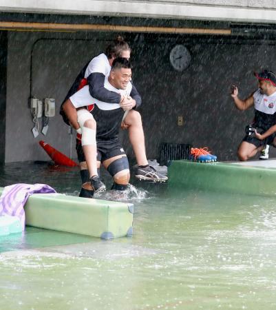 台風19号が接近する中、水がたまった通路でムーアを背負い練習に臨むラグビー日本代表の具智元=12日午前、東京都内