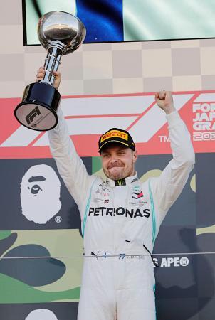 F1日本GPで優勝し、表彰台でトロフィーを掲げるメルセデスのバルテリ・ボッタス=鈴鹿サーキット