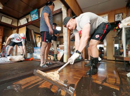 床上浸水した住宅から泥をかき出すラグビーW杯カナダ代表のピーター・ネルソン=13日午後、岩手県釜石市