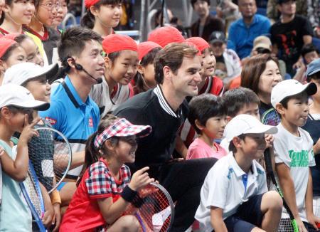 慈善イベントで子どもたちと記念撮影するロジャー・フェデラー(中央)と錦織圭(中央左)=14日、有明コロシアム