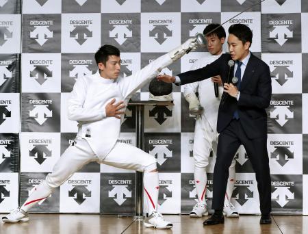 デサントが開発した日本製の競技ウエアについて、見延和靖(左)の実演を交えながら説明する日本フェンシング協会の太田雄貴会長。右奥は加納虹輝=16日午後、東京都港区