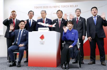 来年3月に開かれる東京五輪の聖火到着式の概要が発表され、笑顔で記念写真に納まる野村忠宏さん(前列左)、吉田沙保里さん(同右)ら=25日午後、東京都中央区