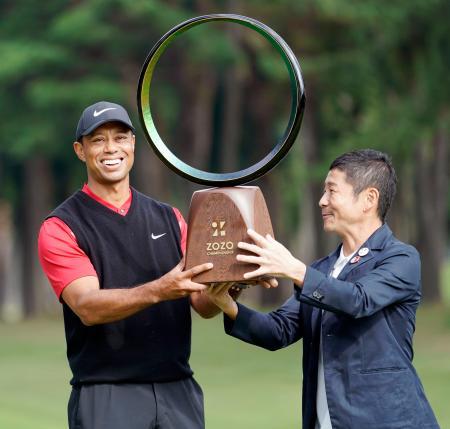 米男子ゴルフツアー大会として日本初開催のZOZOチャンピオンシップで優勝を決め、前沢友作氏からトロフィーを受け取るタイガー・ウッズ=28日、千葉県の習志野CC