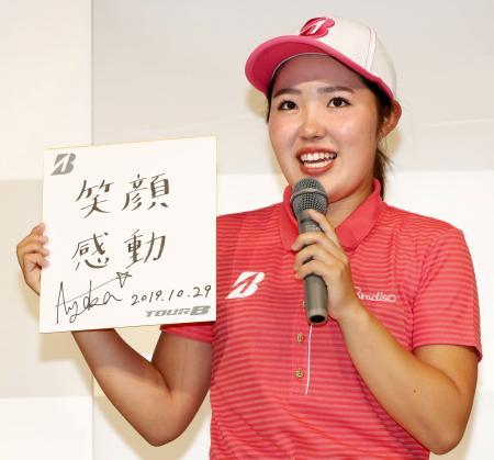 「笑顔 感動」と書かれた色紙を手に、記者会見する女子ゴルフの古江彩佳=29日午前、東京都内